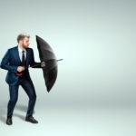 Mann hält schützend einen Regenschirm vor sich.
