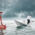 Symbolbild- Mann steht in einem Papierboot an einer Boje