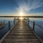 Steg am Wasser bei Sonnenaufgang